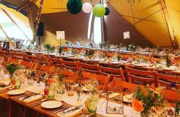 Tipi wedding with rustic furniture and green glassware