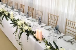 Bright white wedding top tables with grey napkins and green foliage runners with white roses and candles