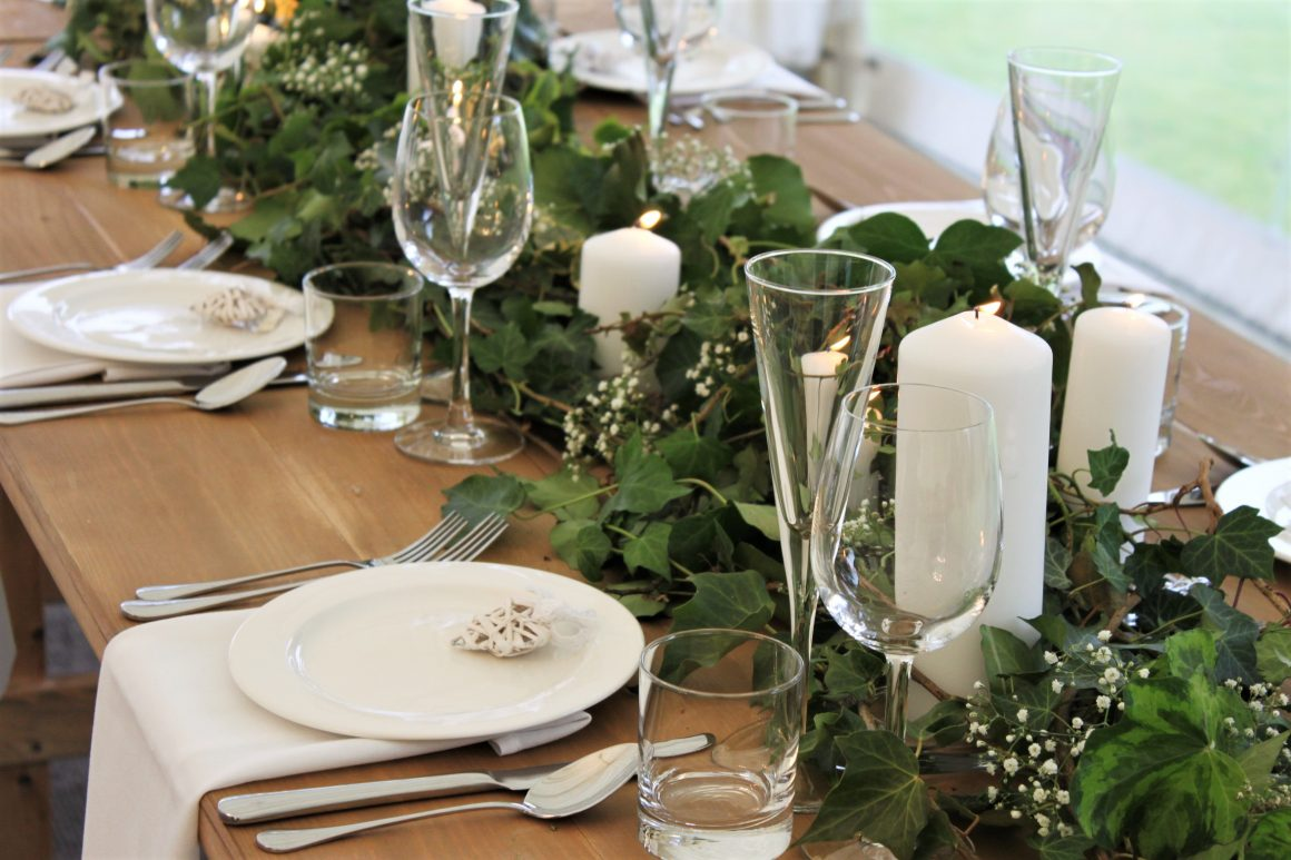 Wide rustic wooden trestle tables with botanical theme, white pillar candles and ivory crockery