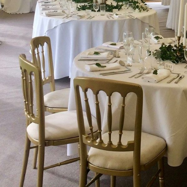 Gilt gold spindle back banqueting chairs with ivory seat pads and ivory table linen