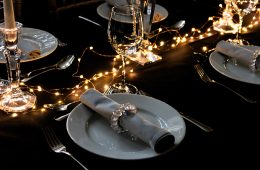 Party table settings with black cloths, grey napkins and fairy lights