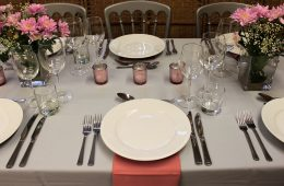 Grey and pink wedding table settings with pink tea light holders and pink flowers