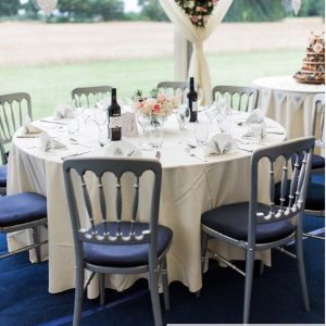 Silver spindle back banqueting chairs with blue seat pads at a blue & ivory themed wedding