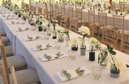 July wedding with small glass bottles, spirit glasses and banquet dining with white table linen