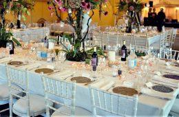 Colourful table settings in an Indian lined marquee, with bright flowers and finer range of tableware