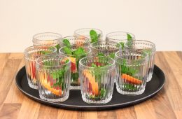 A black bar tray with ribbed cocktail glasses filled with fruit and mint leaves